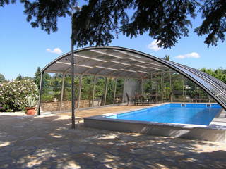 Retractable pool enclosure RAVENA over hotel pool for guests