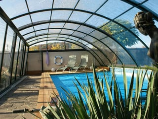 Retractable pool enclosure RAVENA attached on a brick fence