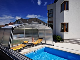 Pool enclosure Venezia in silver color looks great by the modern house