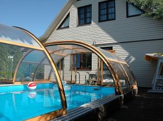 Całkowicie zsunięte zadaszenie basenowe Tropea NEO w wykończeniu imitującym drewno