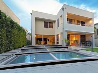 Najniższe zadaszenie basenowe Terra z domem o nowoczesnej architekturze w tle