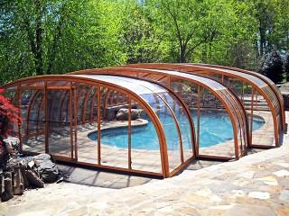 Nietypowy kształt zadaszenia basenowego Laguna NEO o wykończeniu imitującym drewno
