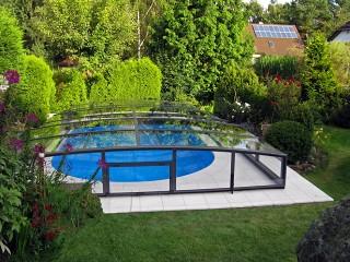 Niewielkie zadaszenie basenowe Viva wygląda doskonale w kwitnącym ogrodzie