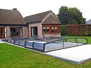 Niskie zadaszenie basenowe Corona z klasycznym domem w tle
