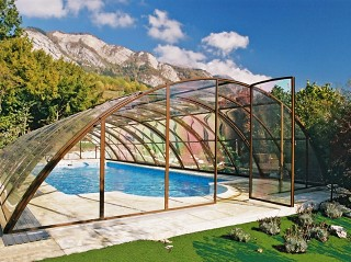 Przesuwne zadaszenie basenowe Universe w kolorze brązowym z pięknym widokiem gór