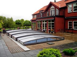 Przesuwne zadaszenie basenowe Viva wygląda doskonale z czerwonym domem w tle