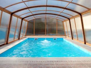 Widok wnętrza zadaszenia basenowego Venezia o wykończeniu imitującym drewno
