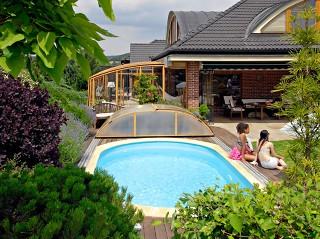 Zabudowa tarasowa Corso oraz zadaszenie basenu Elegant o wykończeniu imitującym drewno