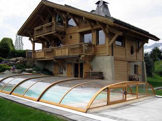 Imitacja drewna używana na ramach zadaszenia basenowego ELEGANT NEO świetnie pasuje do drewnianych domów