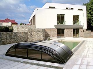 Niskie zadaszenie basenowe ELEGANT z ciemnymi ramami oraz wypalanym, poliwęglanowym wypełnieniem