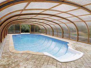 Niskie zadaszenie basenowe LAGUNA NEO wykonane przez Alukov Sp. z o.o. - drewniany kolor i transparentne wypełnienie