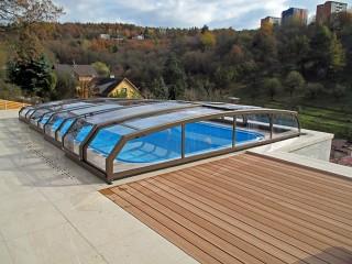 Zadaszenie basenowe Riviera o wykończeniu w kolorze brązowym z pięknym widokiem w tle