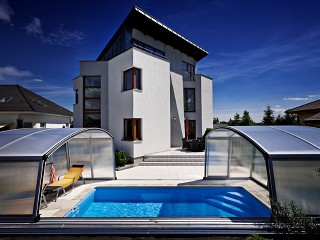 Zadaszenie basenowe Venezia w kolorze srebrnym wygląda doskonale obok domu o nowoczesnej architekturze