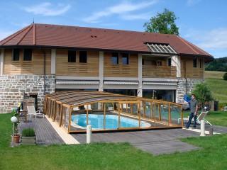 Zadaszenie basenowe Venezia z wykończeniem imitującym drewno pasuje doskonale do domu widocznego w tle