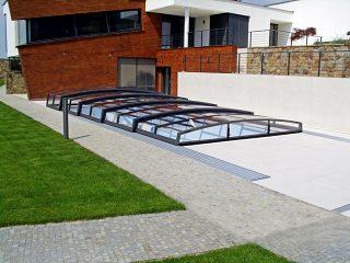 Acoperire retractabila pentru piscina Corona cu casa atipica in fundal