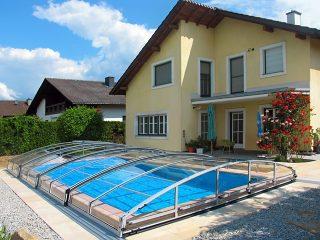 Acoperire  retractabila pentru piscina Imperia cu casa moderna in fundal