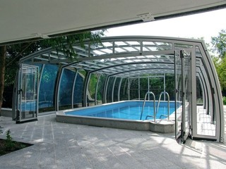 Retractable pool enclosure with open door by a house