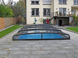 Retractable swimming pool enclosure Riviera protects pool from falling leaves