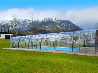 Swimming pool enclosure Omega in silver color with mountains in the background