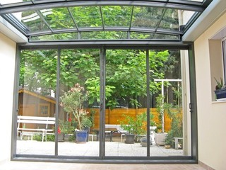 Atypical patio enclosure with front facing wall made of glass