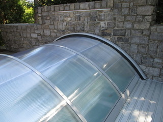 Atypical pool enclosure with ending segment attached to a wall