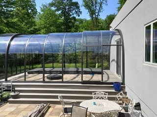 Closed pool enclosure Laguna with sealing profile on house wall