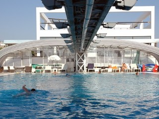 Fully retracted public pool enclosure