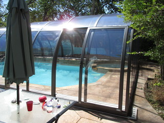 Lateral door in sliding segment of pool enclosure