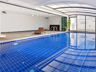 Look into inside pool, half covered with pool enclosure Style