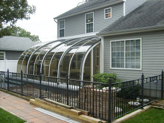 Retractable patio enclosure CORSO Entry attached to a house