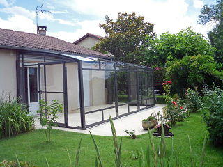 Retractable patio enclosure CORSO - anthracite frames and transparent panels